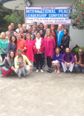 Photo of Participants of the Peace Leadership Conference in front of the welcome banner at the Aurovalley Ashram in Raiwala, India