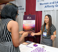 Picture of Sherylle Tan handing out purple ribbons at the WLAG information booth at ILA 2016